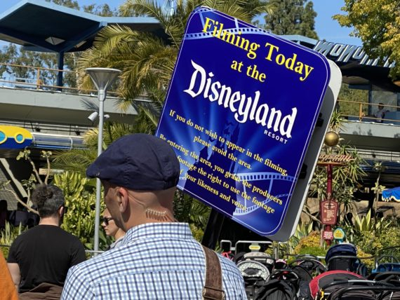 filming at Disneyland sign carried by Cast Member