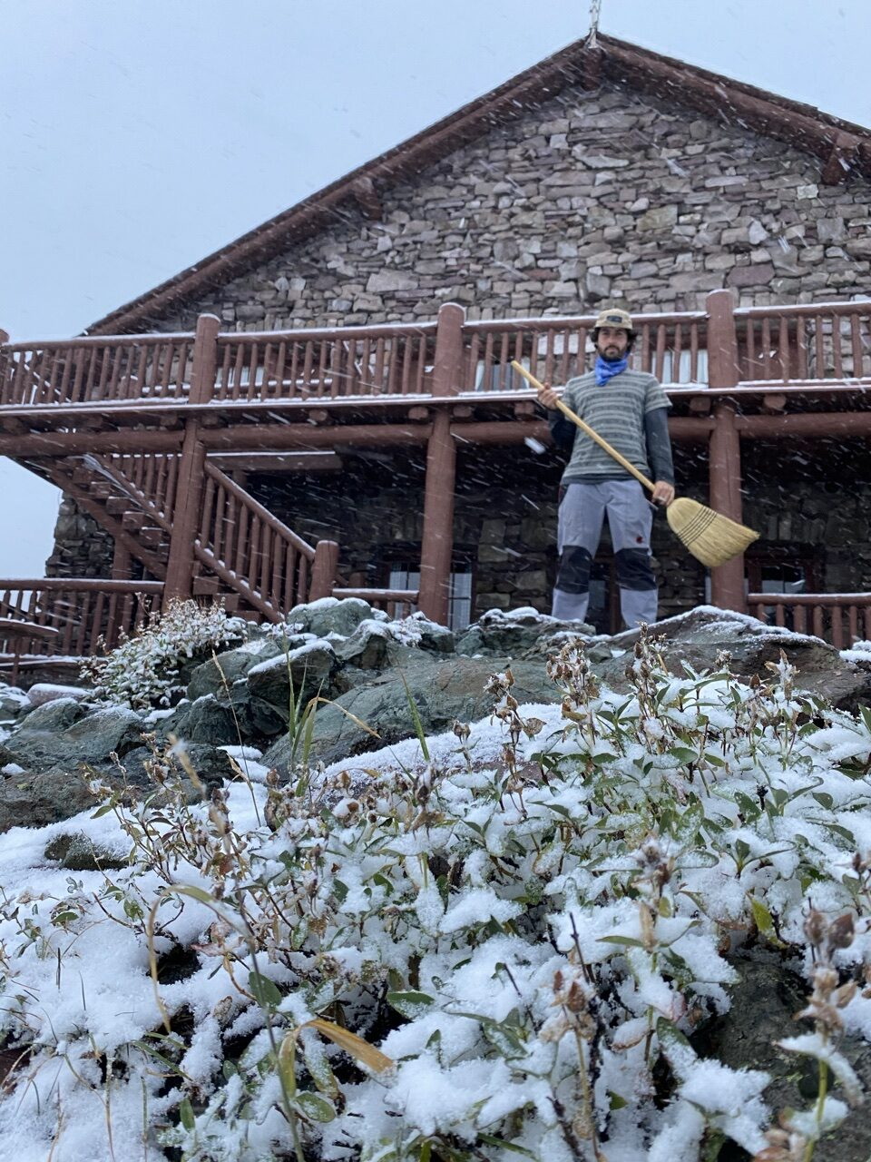 man holding broom in front of Mountain Chalet and snow