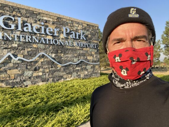 jeff noel wearing a Covid mask in front of Glacier airport sign