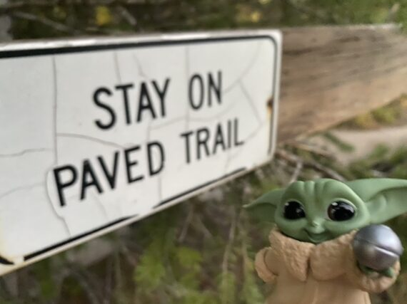 Baby Yoda by hiking trail sign