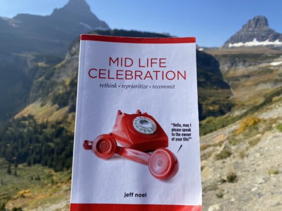 Book in titled Mid Life Celebration Book with mountains in the background