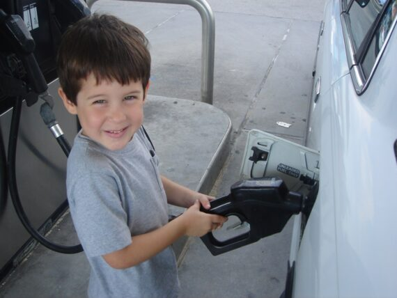 Very young boy pumping gas