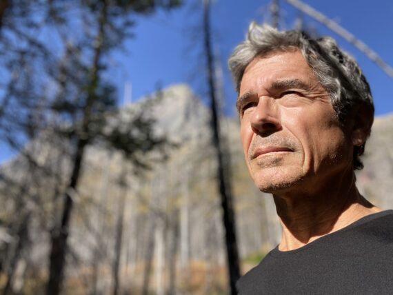 Man in black shirt standing in mountain scene