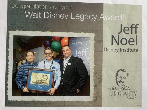 three men holding a Disney recognition plague