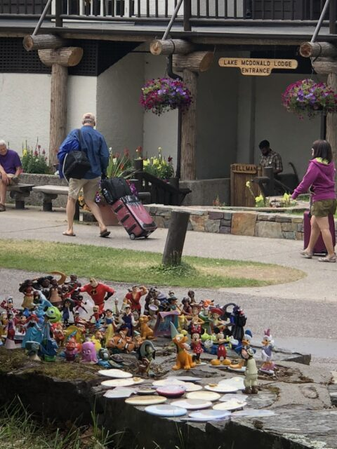 Couple dozen small Disney figurines positioned in front of national Park Lodge
