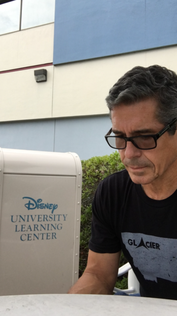 Man sitting next to Disney University trash can