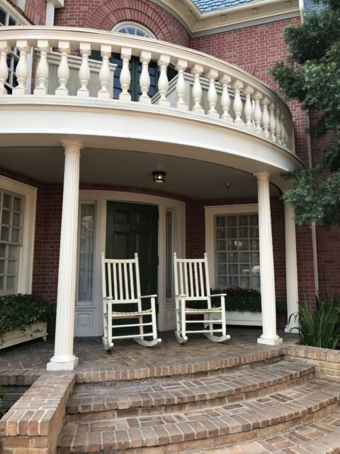 two rocking chairs on brick porch