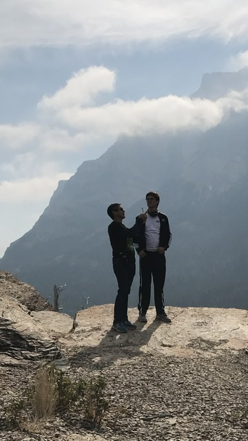 two men standing on a mountain ledge
