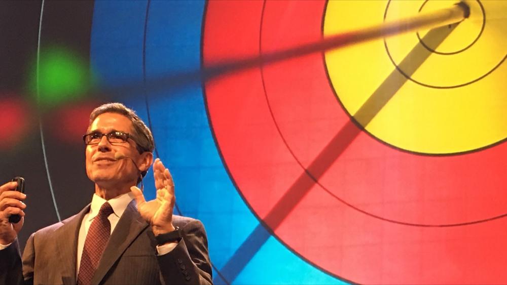 Disney speaker Jeff Noel on stage in front of a giant bullseye
